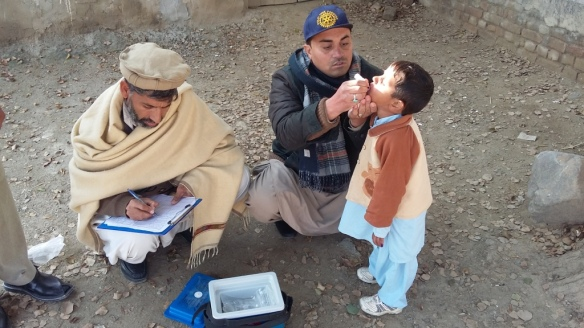 Rotary volunteer administering polio drops to a missed child
