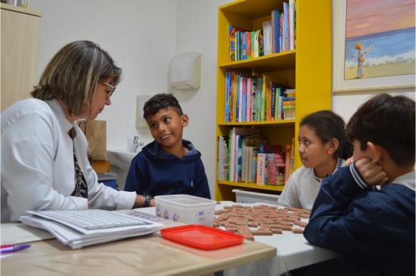 Terapeuta ajuda crianças com jogos para melhorar leitura